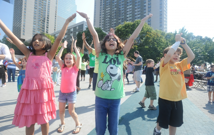 Kids (and some adults)follow the moves of a performer from Asphalt Green.
