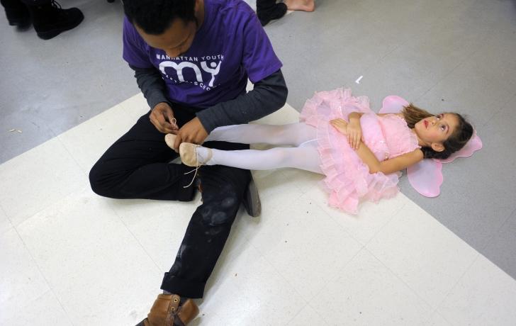 "Before the start of the first of two ""Nutcracker"" performances last month, Manhattan Youth staff member George Ross ties Mina Yavachez's ballet slipper. Photo: Carl Glassman/Tribeca Trib"
