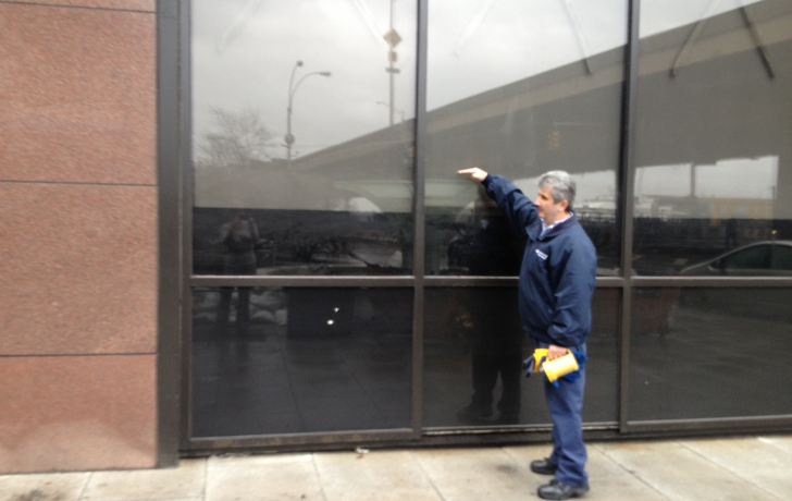 A maintenance worker points to the water mark on the outside of 110 Wall St.