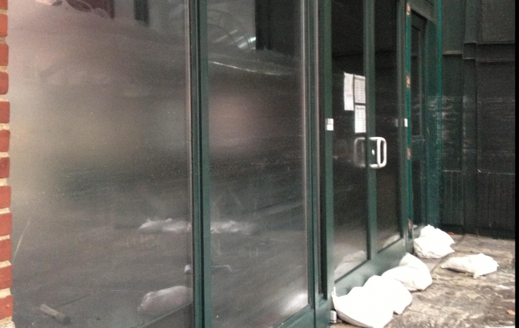 The high water mark is visible on the glass of a Fulton Street store.